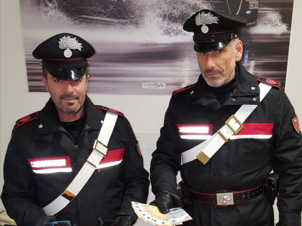 I Carabinieri di Fano mostrano denaro falso e smartphone dopo l'arresto del 19enne di Senigallia